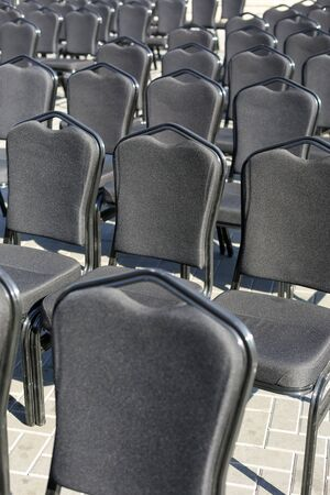 Rows of gray chairs. Street concert, conference, presentation. Vertically framed shot.