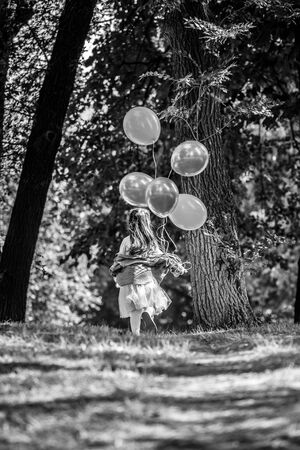 Little cute girl running in the Park with a bunch of balloons. Running back away. The concept of a happy childhood. Vertically framed shot. Фото со стока