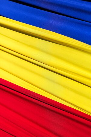 Fabric flag of Romania. Develops in the wind. Vertically framed shot.