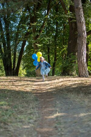 Little cute girl running in the Park with a bunch of balloons. She laughs provocatively. The concept of a happy childhood. Vertically framed shot. Фото со стока