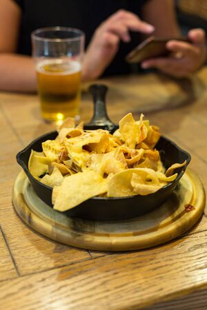 Chips in the pan and beer. In the background, a woman with a smartphone. Vertically framed shot.