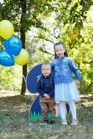 Family life. Brother and sister in the Park. Birthday of a two year old boy. Decor with the number two with lion and balloons. Vertically framed shot. Фото со стока