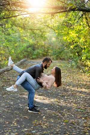 Young beautiful couple in the Park. A man holds a woman in his arms. In the background autumn forest. Vertically framed shot.