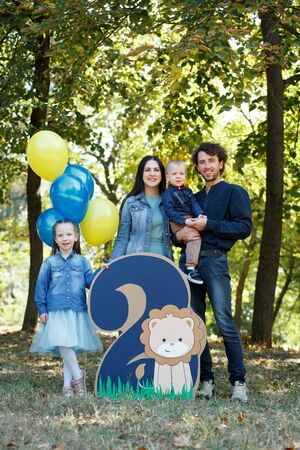 Family life. Portrait of parents and their children in the Park. Birthday of a two year old boy. Decor with the number two with lion and balloons. Vertically framed shot.