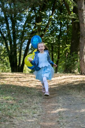 Little cute girl running in the Park with a bunch of balloons. She laughs provocatively. The concept of a happy childhood. Vertically framed shot.