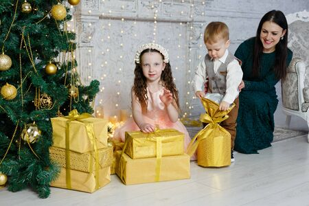 Children and their mother open Christmas gifts. New Year room with at home. Christmas good mood. Lifestyle, family and holiday. Horizontally framed shot.