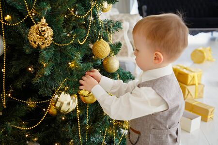 Little boy decorating Christmas tree. New Year room with at home. Christmas good mood. Lifestyle, family and holiday. Horizontally framed shot. Stock Photo