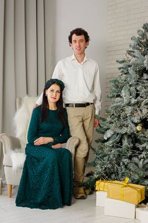 Young married couple at the Christmas tree. New Year room with at home. Christmas good mood. Lifestyle, family and holiday. Vertically framed shot.