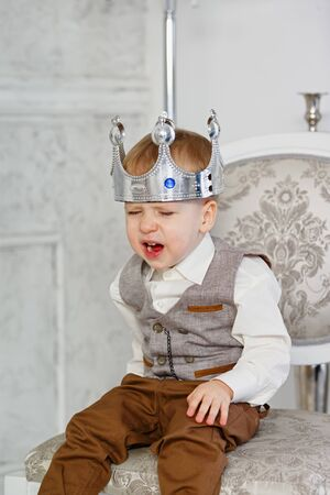 A little boy put a crown on his head and cries. The little Prince was upset. Vertically framed shot.