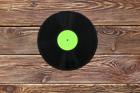 One retro vinyl disc records on wood table background. Green label. Top view. Horizontally framed shot. Banco de Imagens