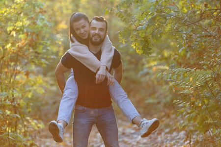 Young beautiful couple and their labrador in the Park. A man holds a woman on his back and she hugs him. Warm autumn evening in the forest. Horizontally framed shot. Stock Photo - 137470608