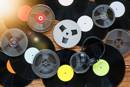 Old vintage bobbins, vinyl records, cassette tapes and headphones on a wood table background. Multicolored labels. Top view. Sun glare. Horizontally framed shot.
