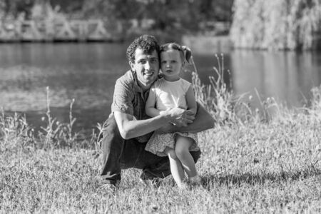 Family portrait. A father hugs his daughter. In the background the lake. Horizontally framed shot.