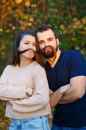 Young beautiful couple in the Park. They fool around and have fun. They make false mustaches out of hair. They are illuminated by a ray of sunlight. In the background autumn forest. Photo.
