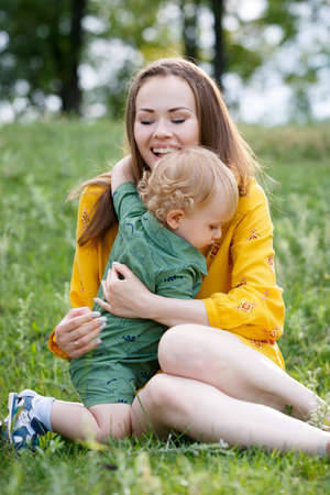 Happy family leisure outdoors. Portrait of smiling young woman holding little toddler son in arms. They are sitting on the green grass. Vertically framed shot.