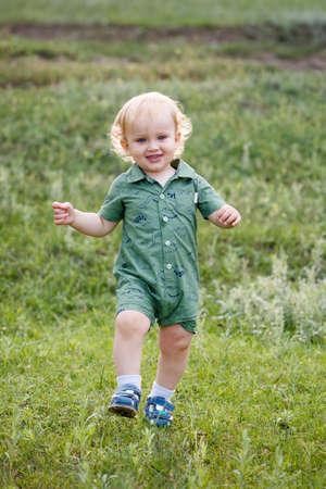 A little boy runs through the grass. Walk in park. Vertically framed shot.