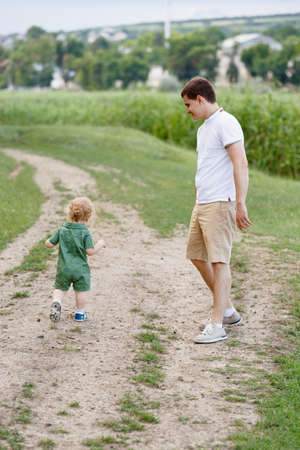 Cute little boy walking along the path on the background of reeds. His father is with him. Walk in park. Family life. Vertically framed shot.