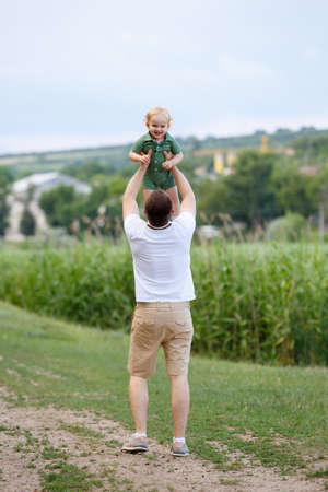 Young father and little son. Dad throws his son up against the background reeds. Walk in park. Family life. Vertically framed shot.