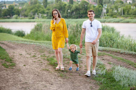 Family life. Portrait of parents and their son on the background of lake. Walk in park. Happy family leisure outdoors. Horizontally framed shot.