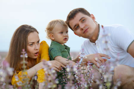 Young family with a baby on a lavender field background. Happy family leisure outdoors. Horizontally framed shot.