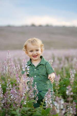 A cute little boy in a lavender field. Happy family leisure outdoors. Vertically framed shot. 版權商用圖片
