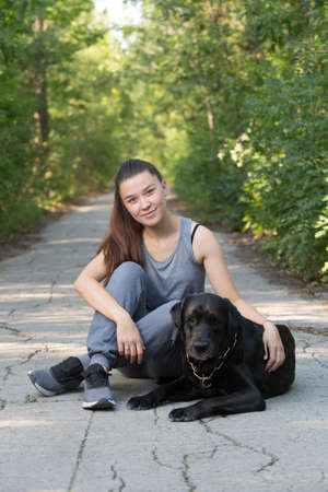 Young attractive sport girl with black Labrador in park. Healthy lifestyle. Walk with favorite pet in wood. Vertically framed shot.