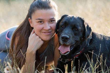 Young attractive sport girl with black Labrador in park. Healthy lifestyle. Walk with favorite pet in wood. Horizontally framed shot. 版權商用圖片