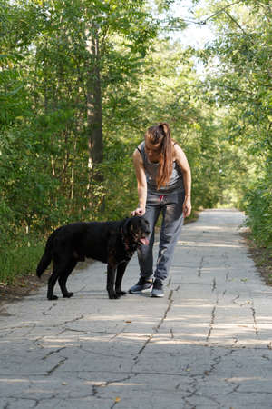 Young attractive sport girl walking with black Labrador in park. Healthy lifestyle. Walk with favorite pet in wood. Vertically framed shot.