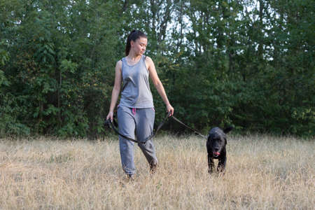 Young attractive sport girl walking with black Labrador in park. Healthy lifestyle. Walk with favorite pet in wood. Horizontally framed shot. 版權商用圖片