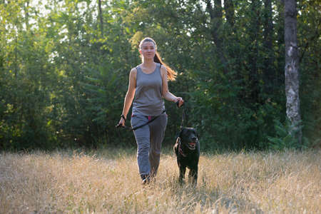 Pretty girl and a black dog in park. Sports lifestyle. Horizontally framed shot.
