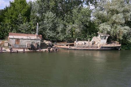 Rusty old ship on the banks of the river. Horizontally framed shot. 版權商用圖片