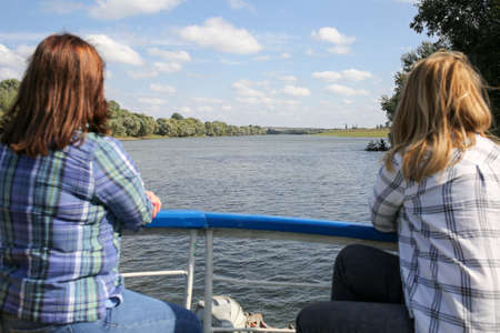 Two women sit back on bow of yacht and look at the river. Lesbians ride on a riverboat. Horizontally framed shot.
