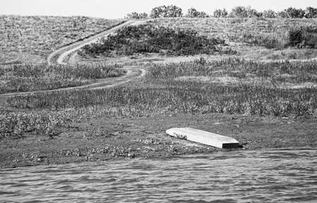 Overturned boat on the river Bank. The trail goes into the distance. Horizontally framed shot. 版權商用圖片