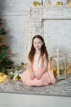 Little cute girl sitting at the Christmas tree. New Year room. Christmas good mood. Lifestyle, family and holiday. Horizontally framed shot. Vertically framed shot. 版權商用圖片