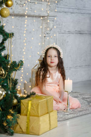 Little cute girl sitting at the Christmas tree. New Year room. Christmas good mood. Lifestyle, family and holiday. Vertically framed shot.