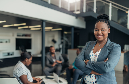 Portrait of a confident black businesswoman smiling with her arms crossed and all african team in the background Banco de Imagens