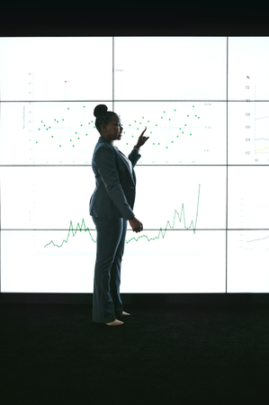 Silhouette of a black african businesswoman giving a presentation at a business conference. Pointing at a large video screen with charts and graphs next to her in a dark room
