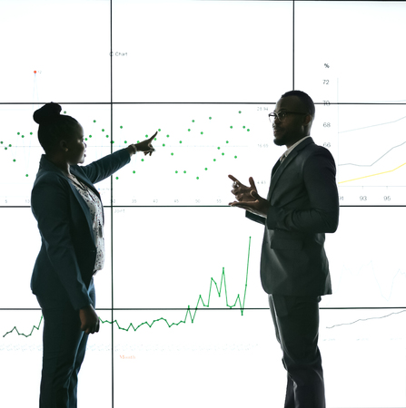 Silhouette of a black african business people giving a presentation conference. Pointing at a large video screen with charts and graphs next to her in a dark room Zdjęcie Seryjne