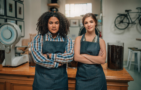 Portrait of confident baristas with arms crossed at the coffee shop