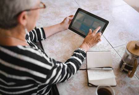 Top view of mature woman making notes interacting on a digital tablet Stock Photo