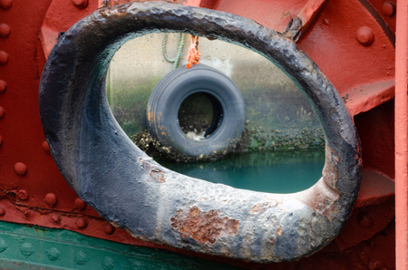 A tyre used for fending ships off the quay is visible in the background through a ship's hawsepipe. Archivio Fotografico