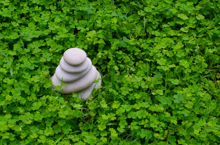 A stone cairn of smoothly eroded pebbles in a lush green bed of clover.