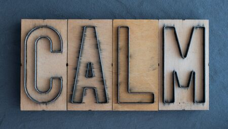 Old wood and steel number plate dies spell out the word CALM