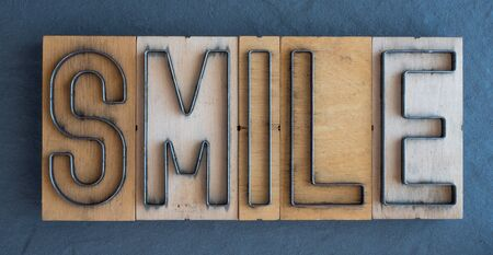 Old wood and steel number plate dies spell out the word SMILE