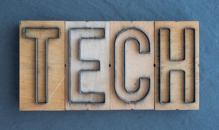 Old wood and steel number plate dies spell out the word TECH