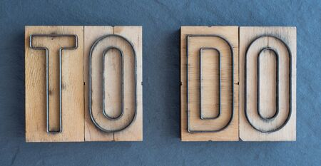 Old wood and steel number plate dies spell out the words TO DO