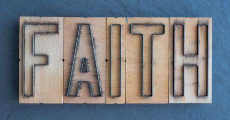 Old wood and steel number plate dies spell out the word FAITH Banco de Imagens