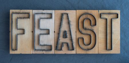 Old wood and steel number plate dies spell out the word FEAST Banco de Imagens