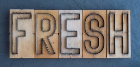 Old wood and steel number plate dies spell out the word FRESH