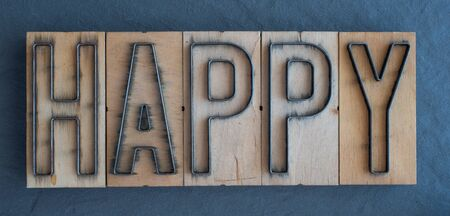 Old wood and steel number plate dies spell out the word HAPPY